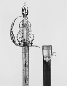 Cavalry Sword  Dated: 1775-85 Culture: English Medium: steel, rayskin, silver Provenance: bought for Royal Armoury from sword-cutler, Bland The sword has a steel hilt, tall oval pommel, acorn tang-button, and a knuckleguard featuring scrolls. The barrel-shaped spiral wooden grip is covered with white rayskin, with silver foil, while the one-edged blade features two fullers and gilt/blued steel panels decorated with strapwork, trophy and sprigs.