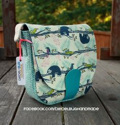 SANDRA BY SWOON is a 70's inspired saddle bag featuring an exterior slip pocket with dart tucks for extra room and an interior zippered pocket. She is easy to carry with an adjustable long crossbody strap. can be made in either or both non-fraying vinyl or woven fabric. A magnetic snap closure is sewn into the bottom seam to flip up and attach to the exterior of the flap, keeping your belongings secure and the bag easy to open and close.