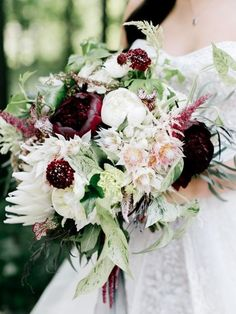A loose bouquet of burgundy dahlias, pale blush O'Hara garden roses, peachy blush Juliet garden roses, blushing bride protea, burgundy astrantia, burgundy sacbiosa, blush astilbe, blush nerines, sivler dollar eucalyptus, seeded eucalyptus, agonis, nagi, and plumosa wrapped in ivory ribbon with the stems showing