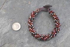 Autumn Dragon Scales Kumihimo Artisan Bracelet #bracelet #kumihimo #kumihimobracelet #artisan #artisanbracelet #handmade #woven #handwoven #handknotted #dragon #dragonscales #magatama #oneofakind #lightweight #flexible #iridescent #rich #warm #red #garnet #burgundy #gunmetal #leather #leatherbutton #beadedbracelet #boho #bohemian #unique #japanese #japaneseweaving
