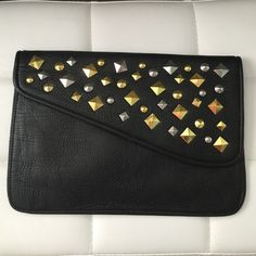 """STUDDED CLUTCH BAG BRAND NEW, NEVER USED. BLACK CLUTCH BAG WITH GOLD & SILVER STUD DETAIL. MAGNETIC CLOSURE ON FLAP. ZIPPER POCKET INSIDE OF BAG. MEASURES 12"""" WIDTH & 8.5"""" TALL. ONE OF THE GOLD STUDS HAS A MINOR SCUFF ON IT. Bags Clutches & Wristlets"""