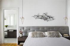 cool grey bedroom, bed with custom grey fabric headboard,  brass frame lights