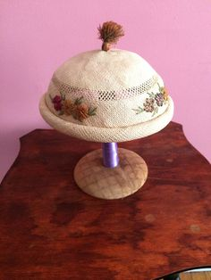 """This sweet little summer straw hat was worn tilted on the head. (see last photo) . Weave is small and tight. Round crown, with a 1"""" rolled brim. Colorful straw flowers are sewn around the hat in four places. A straw tassel completes the look. A cream color rayon satin headband is sewn inside of the hat. Unlined. Measures 22"""" circumference. Good vintage condition.   eBay!"""