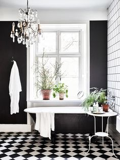 Industrial inspired bathroom with a black contrast wall, a vintage chandelier, and a clawfoot tub