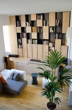 Este pequeno apartamento, projetado por Mickaël Martins Afonso e L'atelier miel, possui algumas ideias inteligentes de design. A principal delas é um grande móvel de madeira que organiza muitas funções do apartamento. Nele, encontramos nichos para livros, armários, gavetas, bancada para refeições e uma mesa que funciona como home-office. Como já apontamos em dicas para decorar um apartamento pequeno, a marcenaria é um ponto chave, que fará toda a diferença na hora de decorar casas e…