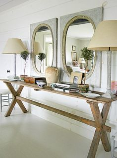 farmhouse style.  beautiful x base console, double mirrors, potted trees, white floors, and planked walls.