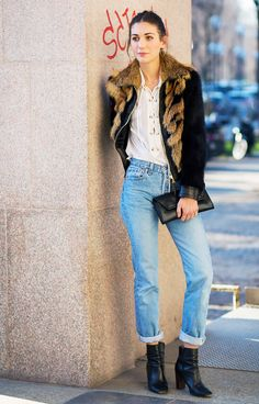 A lace-up top is paired with a fur jacket, cuffed jeans, and black ankle boots