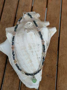 """Diese feine 35.5cm lange Kinder Halskette """"Lotta"""" wurde mit kleinen, anthrazitfarbenen Glasperlen gestaltet. Dazwischen wurden hellgrün-braune facettierte Glasperlen in zwei Grössen hineinplatziert, der Anhänger besteht aus einer frischen, hellgrünen Katzenaugen Glasperle welche mit einem zierlichen Perlkapphütchen versehen ist. Lotta, Beaded Necklace, Jewelry, Fashion, Glass Beads, Cat Eyes, String Of Pearls, Pearl Jewelry, Gifts"""