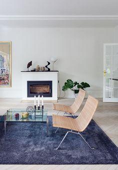 Moderne pejs i stue med lænestole og gulvtæppe