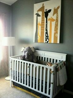 Nursery with cool giraffe painting above crib