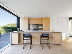 Bates Masi Brings Sophistication to Amagansett Beach House | Polished concrete wraps the kitchen island.  #design #projects #interiordesign interiordesignmagazine
