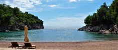 Photo about Photo of two Sunbeds on the sand in front of the Adriatic sea - Sveti Stefan - Montenegro - July 2010. Image of loungers, front, sand - 113951390