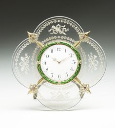 This unusual Fabergé rock crystal desk clock was presented to Queen Victoria by her granddaughter Tsarina Alexandra Feodorovna around 1900. It is engraved with trophies incorporating torches and a quiver as well as musical attributes. The rock crystal panels are divided by four gold arrows set with rubies and diamonds. The white enamel dial is surrounded by a bezel of green enamelled laurel with diamond-set ribbon ties. Workmaster Michael Perchin.