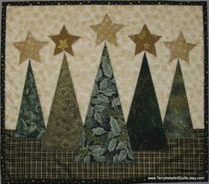 EVERGREEN CHRISTMAS TREES    QUILTED WALL HANGING    Size: W16 x H14 (landscape)    TerryAskeArtQuilts says:  This Seasonal hanging quilt would be a pretty addition to your Holiday decor. A simple, elegant arrangement of evergreen trees in various shades of green and gold, topped with gold stars, are set against a cream and gold snowflake background. Touches of gold metallic add to the holiday theme. The binding fabric is black with gold stars, and the backing fabric is a black on black…