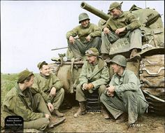 American Journalist and War Correspondent, Ernie Pyle, who is in the center, converses with the crew of a Sherman tank belonging to 191st Tank Battalion at the Anzio Beachhead in 1944.
