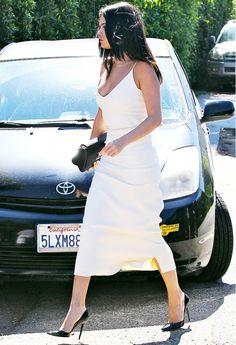 Selena Gomez wears a white slip dress with black pumps and a black bag.