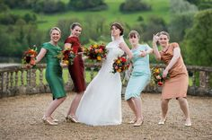 Fun and funky bridesmaids and bride - different coloured bridesmaids dresses and bright floral bouquets, Orchardleigh House, Somerset