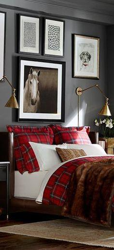 Dark walls, gallery art and cozy bedding.