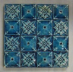 """T & R Boote relief moulded dust pressed tile with a design of sixteen squares alternately containing a flower head and a 'cushion', dark blue glaze, 6"""" square, c1905"""
