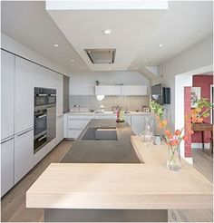 An L-shaped Oak veneered bartop creates a social seating arrangement at the end of the island. Perfect for talking with the cook or enjoying a coffee and reading the paper.  Above the island the bulkhead ceiling features a 'flush-fit' extractor and hidden LED illumination.