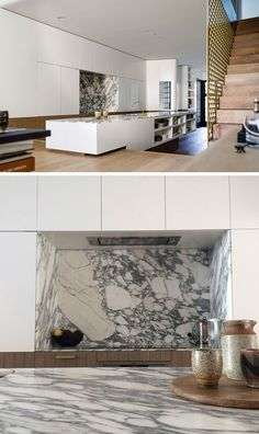 The living room in this modern house sits slightly higher than the kitchen, with the kitchen island straddling across both levels. In the kitchen, Carrara marble has been used for the countertop, and hardware free white and wood kitchen cabinets keep the space streamlined.
