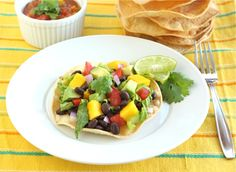 Corn tortillas  1 can of black beans, rinsed and drained and heated up  1 mango, peeled and chopped  1/2 red onion, chopped  2 tomatoes, chopped  Fresh cilantro, chopped  Romaine lettuce, chopped  1 avocado, chopped  Lime wedges  Salsa, if desired
