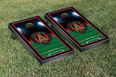 A bean bag toss lawn game complete with a Atlanta United FC style cornhole board, team color duck cloth bags with team logos filled with corn kernels and carrying case for the bags.