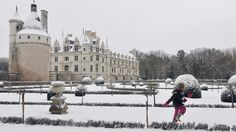 """A child plays in the snow-covered garden of the beautiful Chenonceaux castle in Chenonceaux, western France. """