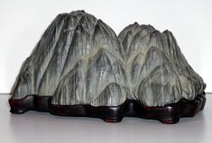 Suiseki--the Japanese art of viewing rocks specially selected.  Note the handcrafted wooden base shaped to fit the rock.