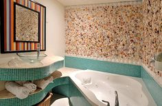 Bath inspired by the sea with real seashells and turquoise green tiles is a signature style of a Key West home decorator