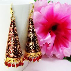 This meenakari cone jhumar is based on a long slim copper cone which is made up of copper polished in high gold and covered in meenakari / enameling in multiple colors. The edges of the cone is decorated with pearl finish colored seeds which enchances the beauty of the earring. The top of the earring is a fish hook for hanging the earring.