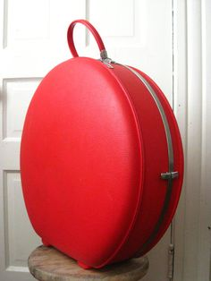 American Tourister round red suitcase.