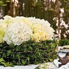 Centerpiece: Soaked florist foam wrapped with ivy, topped with hydrangea and roses. by lebearden