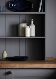 Carefully considered styling with an eclectic mix of handcrafted pottery in complementary blue and neutral and tones bring this bespoke open shelving to life in the Fairford Slate Grey kitchen. From the Shaker Collection by Howdens Joinery.