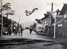 昭和9年 町勢要覧掲載の写真。現在の中央十字路から西方を撮影したもの。奥に長井駅が見える。両側にすずらん灯(街路灯)があるが、駅側と十字路側でデザイン違う。
