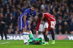Diego Costa of Chelsea and Marcos Rojo of Manchester United stand over as David De Gea of Manchester United as he is injured during The Emirates FA...