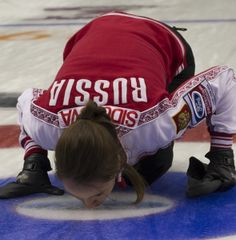 Russian skip Anna Sidorova kisses the ice after her team's bronze-medal victory on Sunday. (Photo, CCA/Michael Burns)