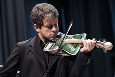 """A violinist with the Paraguayan symphonic orchestra takes part in """"Trash Melodies,"""" a program in which musicians play instruments made out of recycled materials, in Asuncion, Paraguay, on July 28, 2011. The instrument maker, Paraguayan luthier Nicolas Orue, was inspired by the """"Sounds of the Earth,"""" a classical music education project led by Paraguayan musician Luis Szaran."""