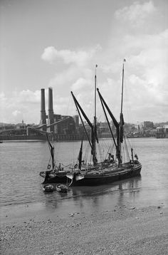 B&W photograph of Thames with the masts with furled sails of two barges at their moorings in the foreground being echoed by the two tall towers of the power station to the left centre ground, on the opposite bank of the river, under a clear sky with puffy white clouds. White Clouds, Clear Sky, River Thames, Towers, Sailing Ships, Seaside, Centre, Nautical, Coastal