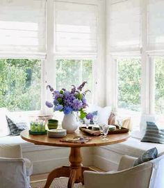 Bright breakfast nook with white roman shades, L-shaped banquette seating and a wood table I want a room with this much sunshine