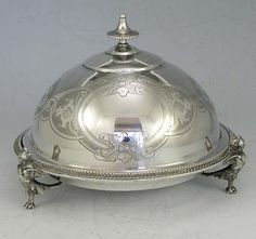 "A Gorham dome shaped coin silver butter dish with original pierced liner. Engraved on the dome. Never monogrammed. Marked lion, anchor, G and 50. The base is supported by three cast winged griffin feet. Height: 5"". Diameter: 6 3/4"""