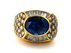 Ringweite: 49. Gewicht: ca. 18,9 g. GG 750. Massiver eleganter Ring mit oval facettiertem Saphir, ca. 6,2 ct, umrahmt von Brillanten und Diamanten im...
