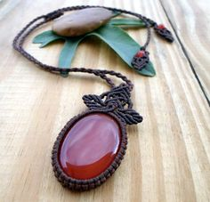 A gorgeous Carnelian cabochon, set with dark brown wax thread in this unisex micro macrame pendant.The pendant is hanged in a handmade cord which is