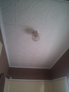 Cover over ugly popcorn ceiling in the bathroom ~ Our R82 Styrofoam Ceiling Tiles installed in a bathroom with brown walls.
