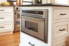 Savvy Kitchen Island Storage - Housing the Microwave Oven Installing a microwave at the end of an island keeps it easy to access, but off of the counter. A bonus: The oven's lower placement makes it handy for kids to make their own popcorn or heat up leftovers.