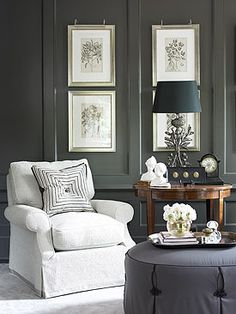 Beautiful Living Room with dark charcoal gorgeous wall paneling, which make the artwork & the white  Chair pop by Blueprint Bliss