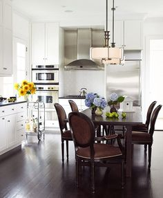 A summer home cleverly combines the kitchen and dining area. Chocolate-brown chairs stand out boldly against white and stainless-steel appliances - Traditional Home® / Photo: Tria Giovan / Design: Larry Laslo