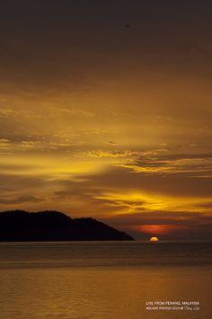 Sun half dipping into sea