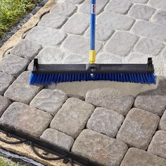 Sweeping Polymeric Sand into Paver Joints.