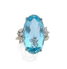 <br /> <b>Bague</b> <br /> En or gris 18k (750), ornée d'une aigue-marine ovale, épaulée d'un bouquet de diamants taillés en navette et en brillant <br /> Poids de l'aigue-marine: 36.94 cts <br /> Tour de doigt: 56, Poids brut: 15.25 g <br /> <br /> An aquamarine, diamond and 18k white gold ring <br /> <br /> <br /> <br />